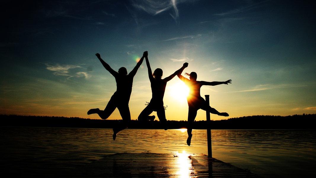 Drei Menschen springen am Meer bei Sonnenuntergang in die Luft. © Utzel-Butzel / photocase.de Foto: Utzel-Butzel / photocase.de