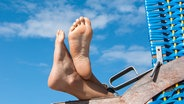 Zwei Füße gucken über die Lehne eines Strandkorbes. © photocase.de / greenpapillon Foto: photocase.de / greenpapillon