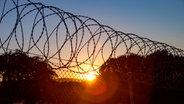 Der Stacheldraht eines Gefängnisses im Sonnenuntergang. © Gelpi / photocase.de Foto: Gelpi / photocase.de