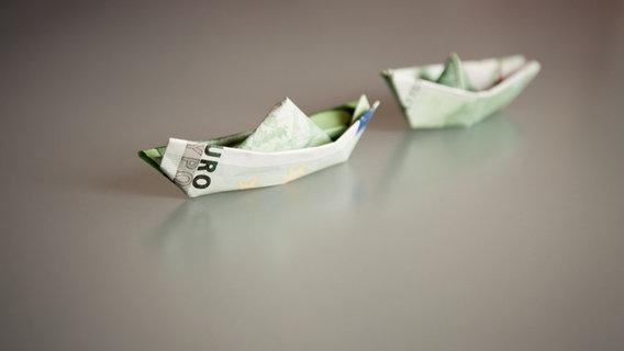 Zwei aus Geldscheinen gefaltete Schiffe liegen auf einem Tisch. © GabiPott / photocase.de Foto: GabiPott