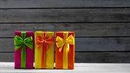 Mehrere eingepackte Geschenke liegen auf einem Tisch. © imago/Westend61 Fotograf: Westend61