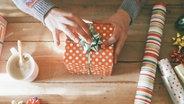 Mehrere eingepackte Geschenke liegen auf einem Tisch. © imago/Westend61 Foto: Westend61
