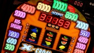 Ein Glücksspielautomat mit bunten Lichtern. © picture alliance/chromorange Foto: CHROMORANGE / H. Richter