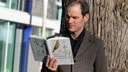 Guido Pauling liest, an einem Baum gelehnt, ein Buch. © NDR