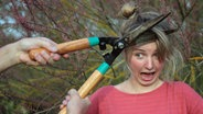 Einer Frau wird mit einer Heckenschere das Haar geschnitten. © Julia Straub / photocase.de Foto: Julia Straub / photocase.de