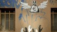 Das Graffiti eines hinfortfliegenden Geldsacks an einer Häuserwand. © morgenroethe / photocase.de