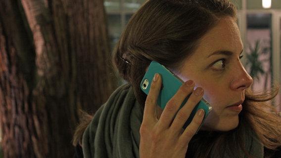 Eine junge Frau schaut im Dunkeln, mit dem Handy am Ohr, verängstigt zurück. © NDR Foto: André Kroll
