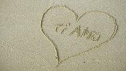 """Das Bild zeigt ein Herz mit der Inschrift """"Ti Amo"""" im Sand. © Imago/Westend61 Fotograf: Westend61"""
