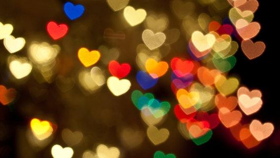 Lichter in Form von Herzen leuchten verschwommen. © picture alliance/chromorange Foto: CHROMORANGE / Barbara Neveu