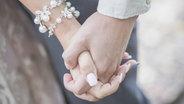 Eine Braut und ein Mann halten Händchen. © imago/Westend61 Fotograf: Westend61