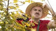 Ein Mann steht fluchend hinter einer Hecke. © picture alliance / Bildagentur-online/Begsteiger