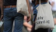 """Eine Frau trägt einen Jutebeutel mit der Aufschrift """"Mehr Sonntag"""" über dem Arm. © dpa"""