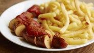 Auf dem Bild ist ein Teller mit einer Currywurst und Pommes zu sehen. © imago/Westend61