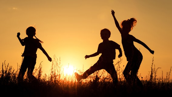 Drei Kinder spielen fröhlich im Sonnenuntergang. © altanaka / photocase.de Foto: altanaka / photocase.de