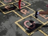 """Zwei Mädchen spielen """"Himmel und Hölle"""". © picture alliance / empics Foto: Dave Thompson"""
