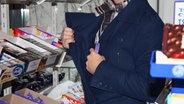 Mann zwischen Regalen steckt sich etwas heimlich in die Tasche.
