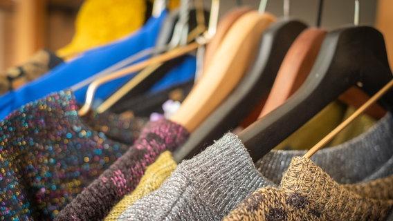 Mehrere Kleiderbügel mit unterschiedlichen Pullovern. © Eliza / photocase.de Foto: Eliza / photocase.de