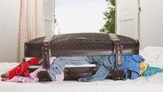 Ein überquillender Koffer liegt auf einem Bett. © imago/Westend61 Fotograf: Westend61