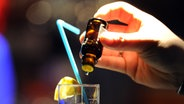 Jemand gibt K.O.-Tropfen in ein Glas. © picture alliance / dpa Fotograf: Achim Scheidemann