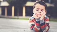 Ein kleiner Junge guckt gelangweilt nach unten. © photocase.de / estherm Foto: photocase.de / estherm