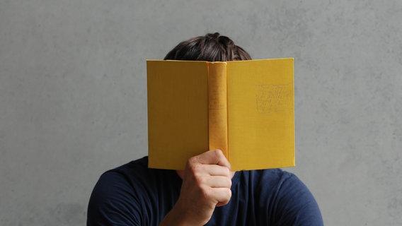 Jemand liest ein gelbes Buch und hält es vor sein Gesicht. © photocase.de / luxuz Foto: photocase.de / luxuz