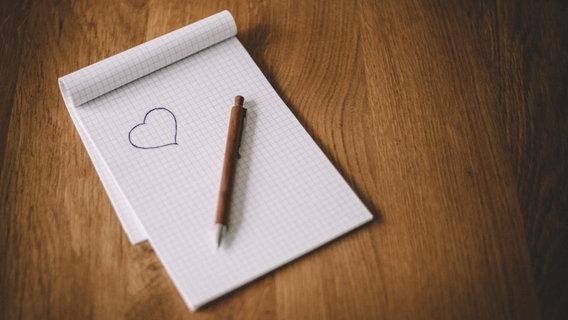 Ein Block mit einem gemalten Herz, auf dem Blatt liegt ein Stift. © tobid / photocase.de Foto: tobid / photocase.de