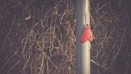Ein Herzluftballon, dem die Luft ausgegangen ist, hängt an einem Laternenpfahl. © imago/Westend61 Foto: Westend61