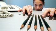 Eine Frau richtet Bleistifte genauestens aus ©  picture alliance / dpa Themendienst