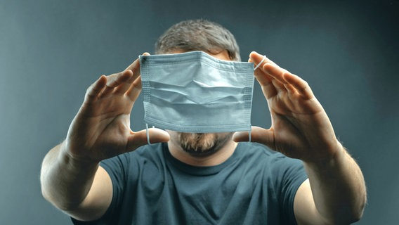 Ein Mann hält eine Gesichtsmaske vor sein Gesicht.  © Brilliant Eye / Photocase.D Foto: Brilliant Eye / Photocase.t