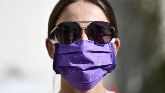 Eine junge Frau trägt eine Gesichtsmaske und eine Sonnenbrille. © picture alliance/dpa Themendienst Foto: Kirsten Neumann