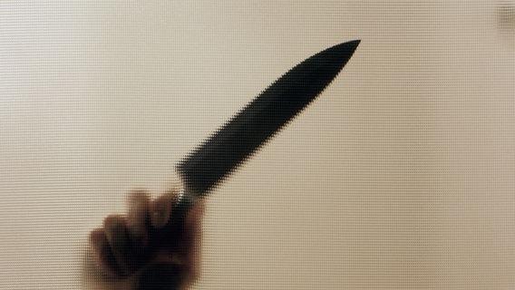 Eine Hand hält ein Messer hinter einer Scheibe fest. © photocase.de / DWerner Foto: photocase.de / DWerner