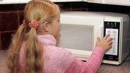 Kleines Mädchen bedient Mikrowelle © dpa - Report