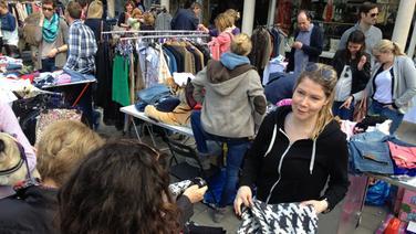 Frau zeigt Ware auf Flohmarkt. | Susan Hammann