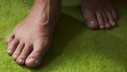 Zwei nackte Füße betreten einen grünen Teppich. © picture-alliance/chromorange