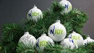 Acht signierte N-JOY Weihnachtskugeln liegen auf einem Adventskranz. © NDR/N-JOY Foto: Anthrin Warnking