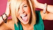 Eine junge Frau haelt sich ausgelassen schreiend den Kopf. ©  picture alliance / blickwinkel/McPHOTO Foto: McPHOTO