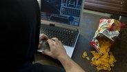 Ein Mann sitzt in einer abgedunkelten Mietwohnung und spielt ein Computerspiel. © picture alliance / dpa Themendienst