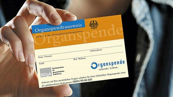 Eine Frau hält einen Organspendeausweis in die Höhe. © BZGA Foto: BZGA