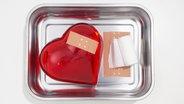 Ein Herz mit Pflaster darauf  liegt in einer Schale. © PIcture-Alliance Foto: beyond/Junos