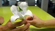 Eine, aus Papier gefaltete Blume.