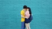 Ein junges Paar küsst sich vor einer blauen Wand. © imago/Westend61