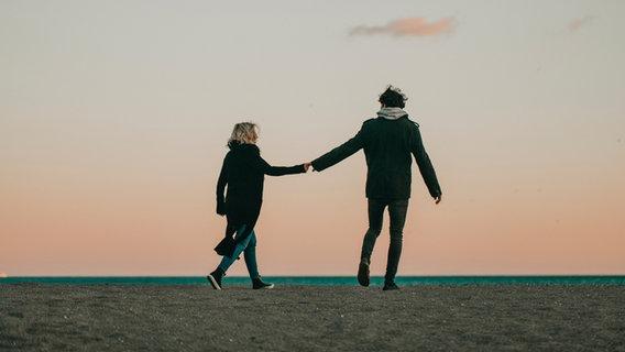 Ein Paar spaziert Hand in Hand auf einem Deich. © daviles / photocase.de Foto: daviles / photocase.de