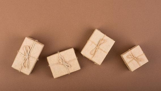Vier in Packpapier eingepackte Pakete liegen auf braunem Untergrund. © Good Mood / photocase.de Foto: Good Mood / photocase.de