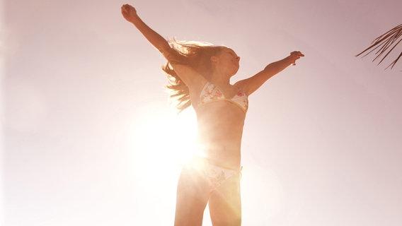 Junge Frau springt am Strand in die Luft © picture alliance