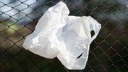 Eine weggeworfene Plastiktüte hängt in einem Zaun fest. © dpa - Bildfunk Foto: Patrik Pleul/dpa