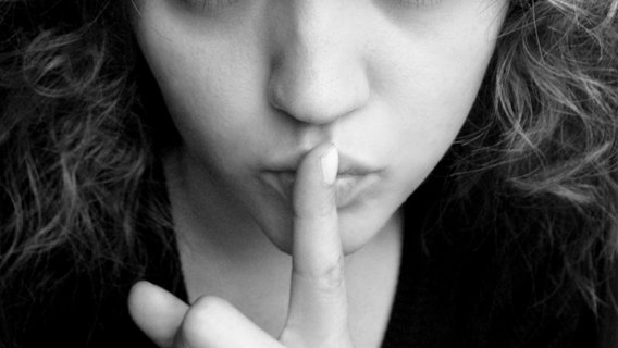Eine Frau hebt den Zeigefinger an den Mund. © g.sperling / photocase.de Foto: g.sperling / photocase.de