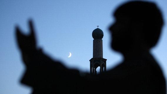 Mann vor Moschee mit Mondsichel im Hintergrund. © EPA