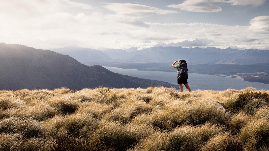 Ein Rucksack-Tourist steht an der Küste und schaut in die Ferne. © maikirmscher / Photocase; Foto: maikirmscher / Photocase;