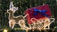 Ein beleuchteter Rentierschlitten auf einem Weihnachtsmarktstand. © picture alliance/imageBROKER Foto: Movementway