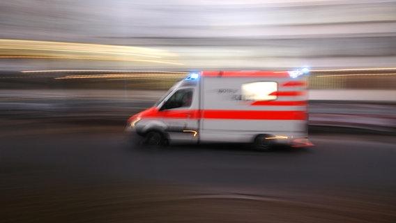 Ein unscharf erkennbarer, schnell fahrender Rettungswagen. © picture alliance/imageBROKER Foto: Helmut Meyer zur Capellen